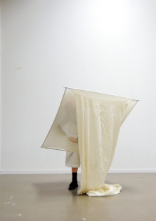 Person performance in white stretchy fabric on a square frame bending forward