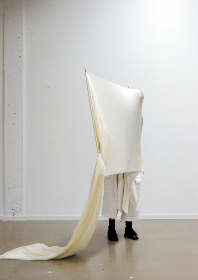 Person performance in white stretchy fabric with frame