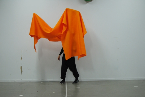 Person Performance draped in an orange textile framed somehow