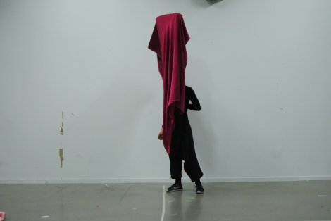 Person performance with a wine-red fabrik on a tall frame
