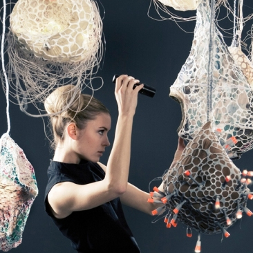 Mysteriusly shaped pods haning from the ceiling, a blonde woman examines with a flashlight