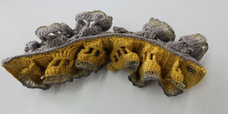 Piece of knitted fabric in yellow and grey.