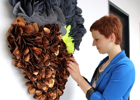 Svenja Keune reorganizing a 3D textile project on a white wall