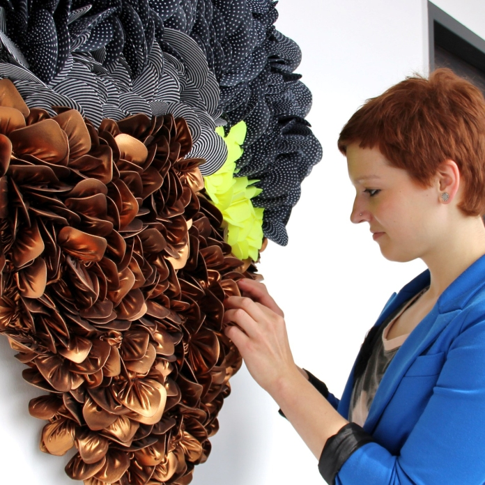 Svenja Keune reorganizing a 3D textile project on a white wall