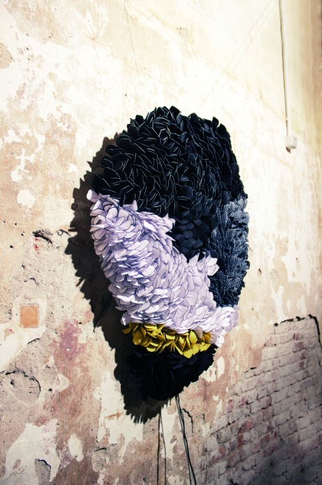 A textile artwork, made of many smaller pieces organised together in a poetic manner, on a rugged wall.