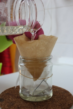 Filtering the solution into a glass jar with textile substrate.