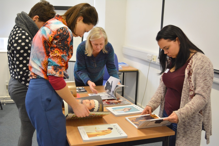 The PhD students look for inspiration in a pile of fashion magazines, a presentation form that might be useful to their research projects or future products.